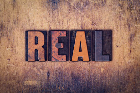 realism: The word Real written in dirty vintage letterpress type on a aged wooden background.