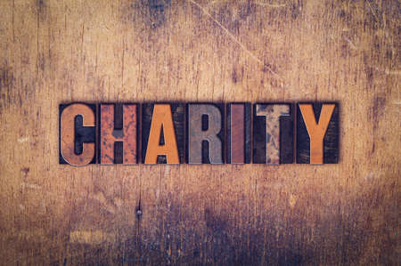 handout: The word Charity written in dirty vintage letterpress type on a aged wooden background. Stock Photo