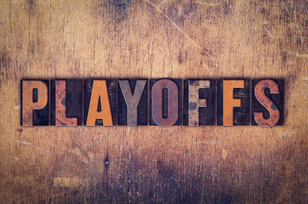 playoffs: The word Playoffs written in dirty vintage letterpress type on a aged wooden background.