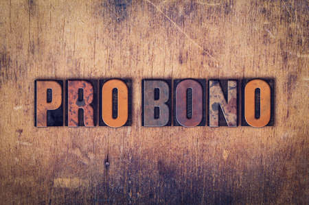 The word Pro Bono written in dirty vintage letterpress type on a aged wooden background.