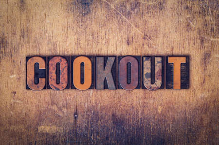 pig roast: The word Cookout written in dirty vintage letterpress type on a aged wooden background. Stock Photo