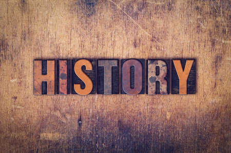 """The word """"History"""" written in dirty vintage letterpress type on a aged wooden background."""