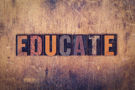 The word Educate written in dirty vintage letterpress type on a aged wooden background.