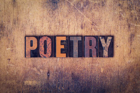 The word Poetry written in dirty vintage letterpress type on a aged wooden background.