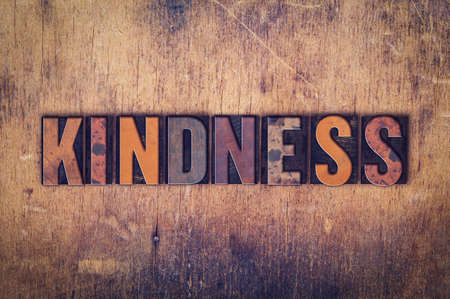 The word Kindness written in dirty vintage letterpress type on a aged wooden background.
