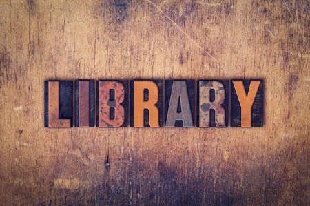 media center: The word Library written in dirty vintage letterpress type on a aged wooden background. Stock Photo