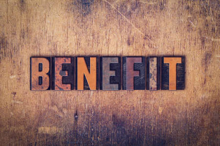 insurance themes: The word Benefit written in dirty vintage letterpress type on a aged wooden background.