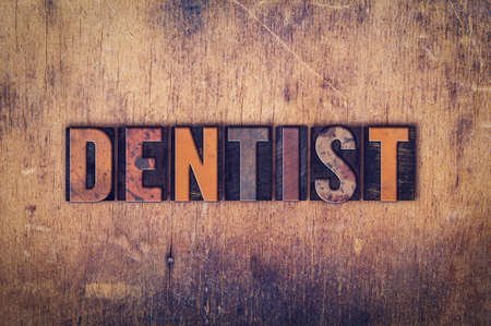 "The word ""Dentist"" written in dirty vintage letterpress type on a aged wooden background."