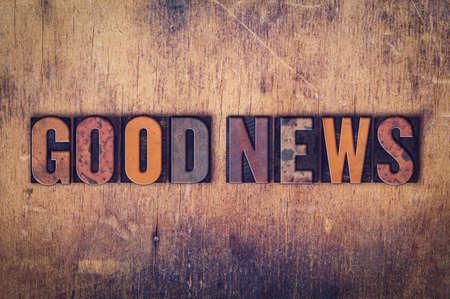 """Het woord """"Good News"""" geschreven in vuile vintage boekdruk type op een oude houten achtergrond."""