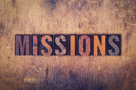 The word Missions written in dirty vintage letterpress type on a aged wooden background.