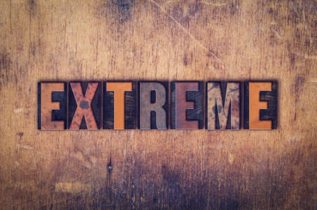 adverse: The word Extreme written in dirty vintage letterpress type on a aged wooden background.