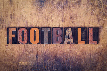 superbowl: The word Football written in dirty vintage letterpress type on a aged wooden background.
