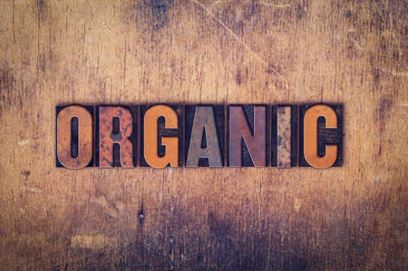 The word Organic written in dirty vintage letterpress type on a aged wooden background. Stock Photo
