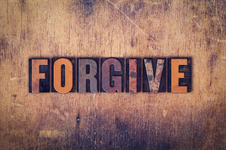 amend: The word Forgive written in dirty vintage letterpress type on a aged wooden background.