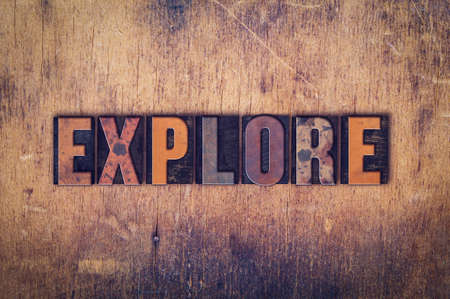 The word Explore written in dirty vintage letterpress type on a aged wooden background. Banco de Imagens