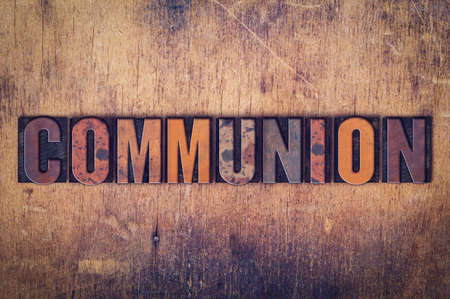 """Het woord """"Communie"""" geschreven in vuile vintage boekdruk type op een oude houten achtergrond. Stockfoto"""