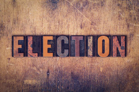 elected: The word Election written in dirty vintage letterpress type on a aged wooden background.