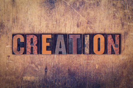 The word Creation written in dirty vintage letterpress type on a aged wooden background.