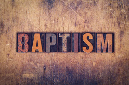 baptize: The word Baptism written in dirty vintage letterpress type on a aged wooden background.