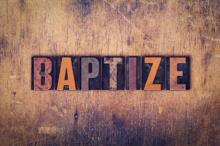 baptize: The word Baptize written in dirty vintage letterpress type on a aged wooden background.