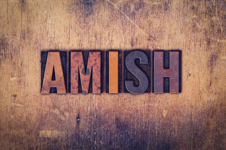 The word Amish written in dirty vintage letterpress type on a aged wooden background.