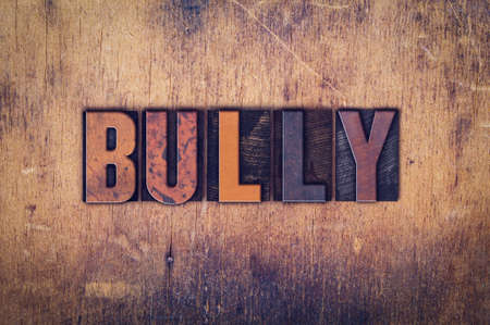 torment: The word Bully written in dirty vintage letterpress type on a aged wooden background.