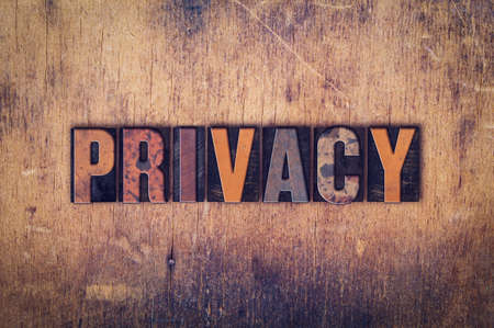 seclusion: The word Privacy written in dirty vintage letterpress type on a aged wooden background. Stock Photo