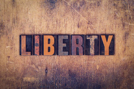 liberties: The word Liberty written in dirty vintage letterpress type on a aged wooden background.
