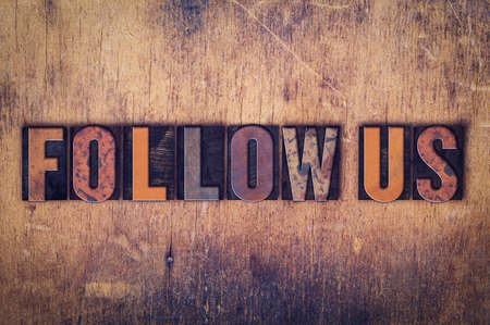 The word Follow Us written in dirty vintage letterpress type on a aged wooden background.