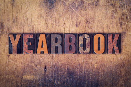 yearbook: The word Yearbook written in dirty vintage letterpress type on a aged wooden background.