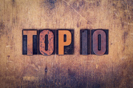 top 10: The word Top 10 written in dirty vintage letterpress type on a aged wooden background. Stock Photo