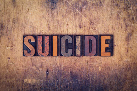 suicidal: The word Suicide written in dirty vintage letterpress type on a aged wooden background.