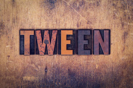 tween: The word Tween written in dirty vintage letterpress type on a aged wooden background. Stock Photo