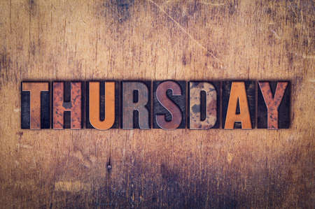 thursday: The word Thursday written in dirty vintage letterpress type on a aged wooden background.