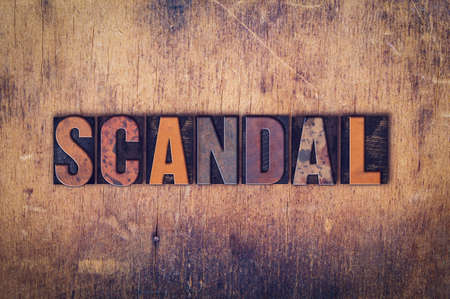 scandalous: The word Scandal written in dirty vintage letterpress type on a aged wooden background.