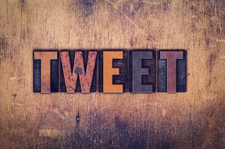 The word Tweet written in dirty vintage letterpress type on a aged wooden background.
