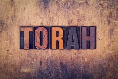 The word Torah written in dirty vintage letterpress type on a aged wooden background.