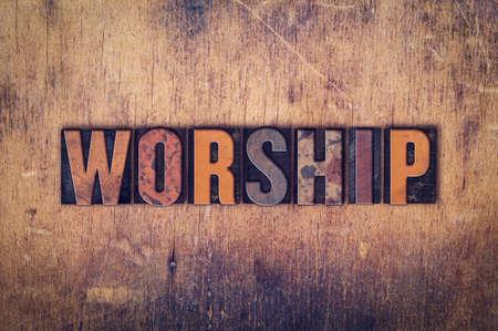"""Het woord """"Worship"""" geschreven in vuile vintage boekdruk type op een oude houten achtergrond. Stockfoto"""