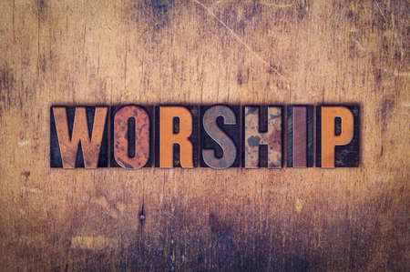 catholic church: The word Worship written in dirty vintage letterpress type on a aged wooden background.