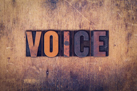 spokesperson: The word Voice written in dirty vintage letterpress type on a aged wooden background. Stock Photo