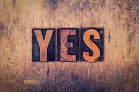 affirmative: The word Yes written in dirty vintage letterpress type on a aged wooden background.
