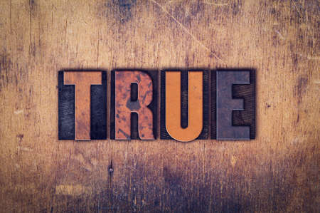 The word True written in dirty vintage letterpress type on a aged wooden background. Imagens
