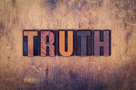 """The word """"Truth"""" written in dirty vintage letterpress type on a aged wooden background."""