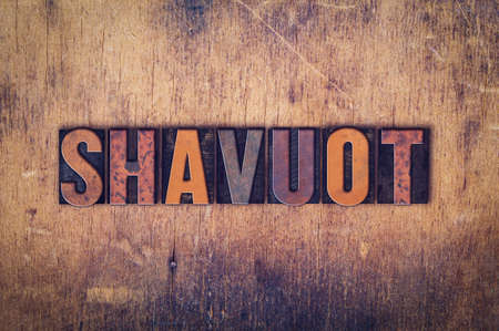 old letters: The word Shavuot written in dirty vintage letterpress type on a aged wooden background. Stock Photo