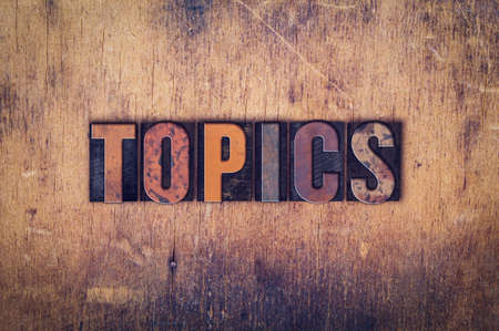 topics: The word Topics written in dirty vintage letterpress type on a aged wooden background.