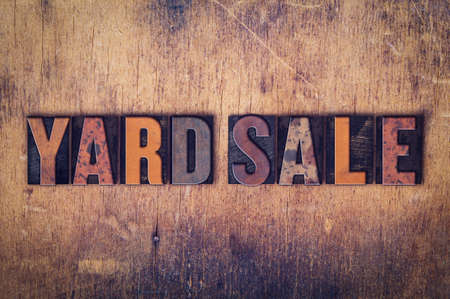 yard sale: The word Yard Sale written in dirty vintage letterpress type on a aged wooden background. Stock Photo