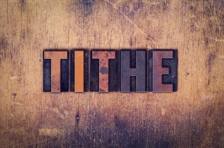 levy: The word Tithe written in dirty vintage letterpress type on a aged wooden background. Stock Photo