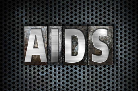 The word AIDS written in vintage metal letterpress type on a black industrial grid background. Stock Photo