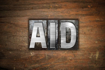 The word Aid written in vintage metal letterpress type on an aged wooden background.