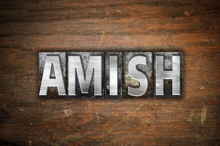 The word Amish written in vintage metal letterpress type on an aged wooden background. Stock Photo